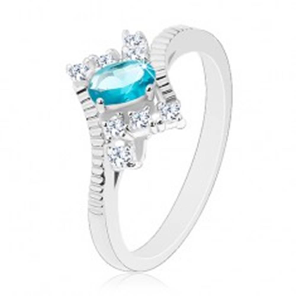 Šperky eshop Prsteň v striebornej farbe, oválny svetlomodrý zirkón, zárezy na ramenách - Veľkosť: 50 mm